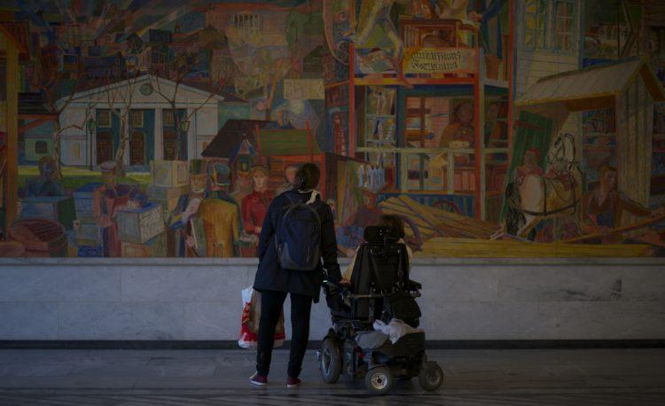 En personlig assistent og arbeidslederen står foran et stort bilde inne i Rådhuset i Oslo. Assistenten har en bærepose i hånda og lener seg mot arbeidslederen mens de analyserer maleriet sammen.