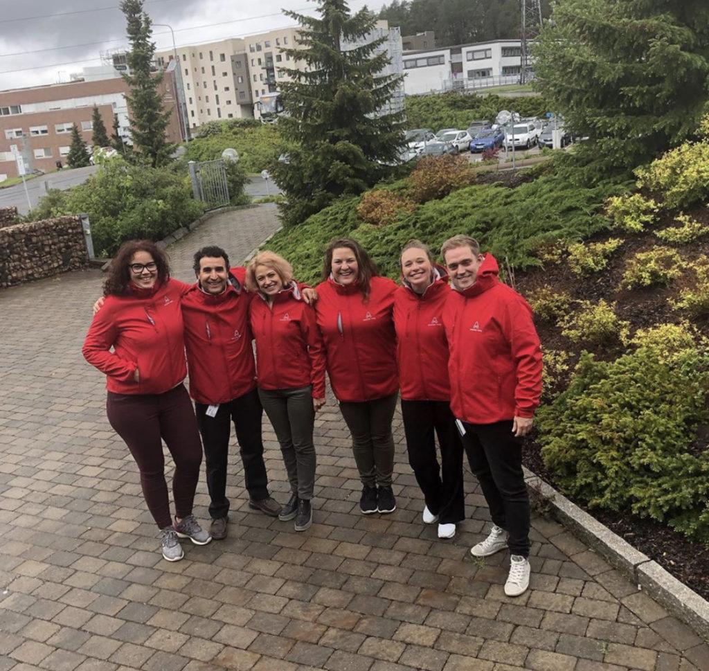 Bilde av seks administrasjonsmedarbeidere i Assister Meg. De står utendørs foran en busk ved en oppkjørsel og smiler med omfavnende tak rundt kolleger.