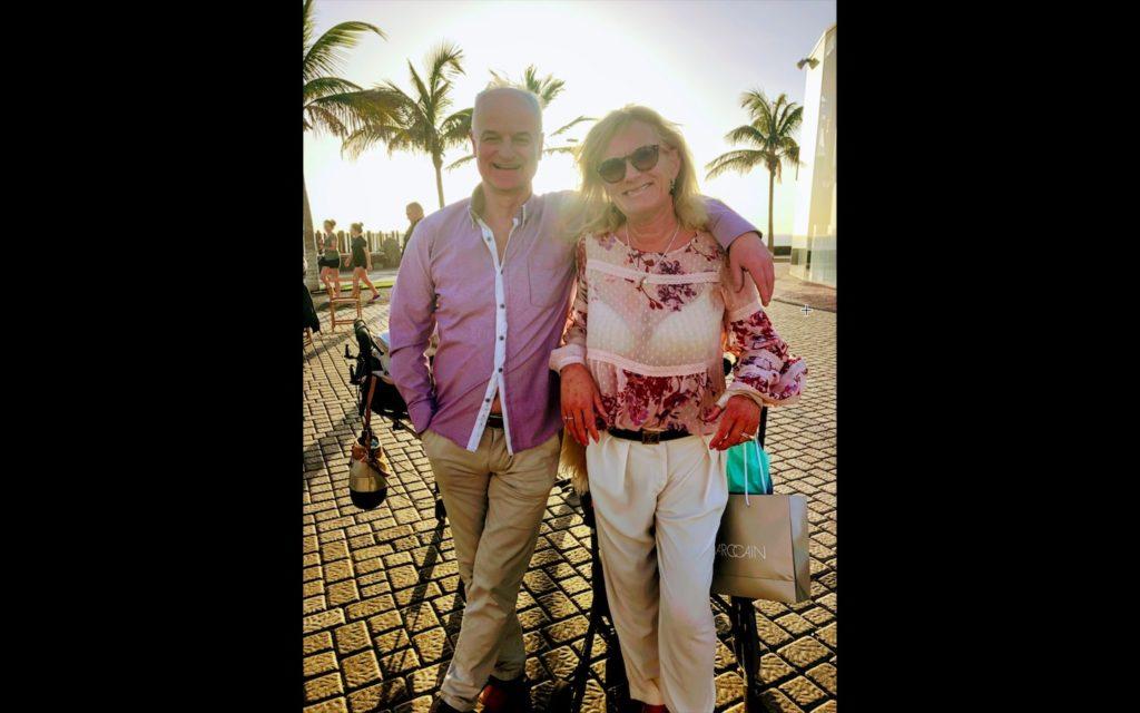 Wenche og Nils Bernt smiler mot kameraet ute i solen med palmer i bakgrunnen