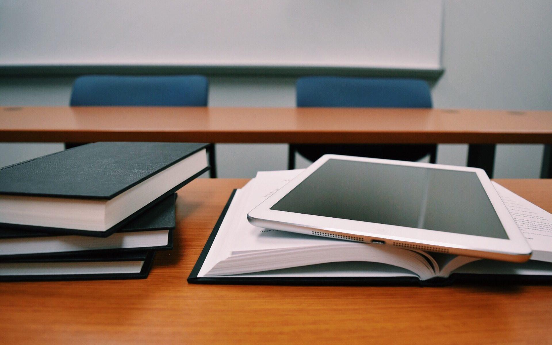 Bilde av tablet og bøker