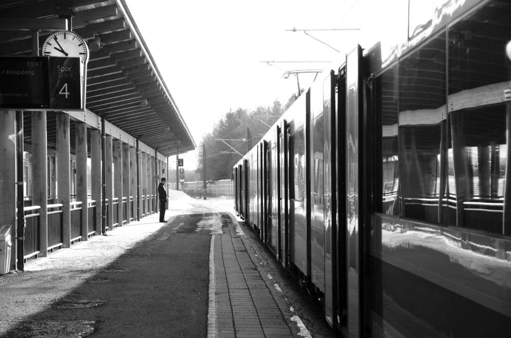 Et sort-hvitt bilde av en konduktør foran et tog på togstasjonen. Klokka viser 6 på hel og toget står i spor 4.